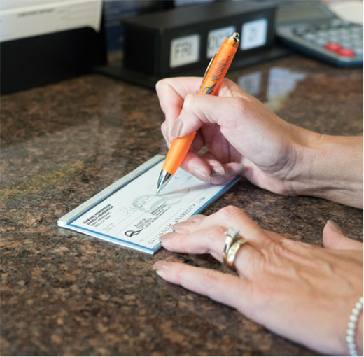 A Woman Writing a Check from Her Personal Checking Account